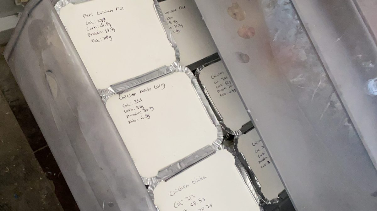 Photo of several small silver foil trays with white lids in a clear freezer drawer. The white lids have various meals and nutrition information written on them.