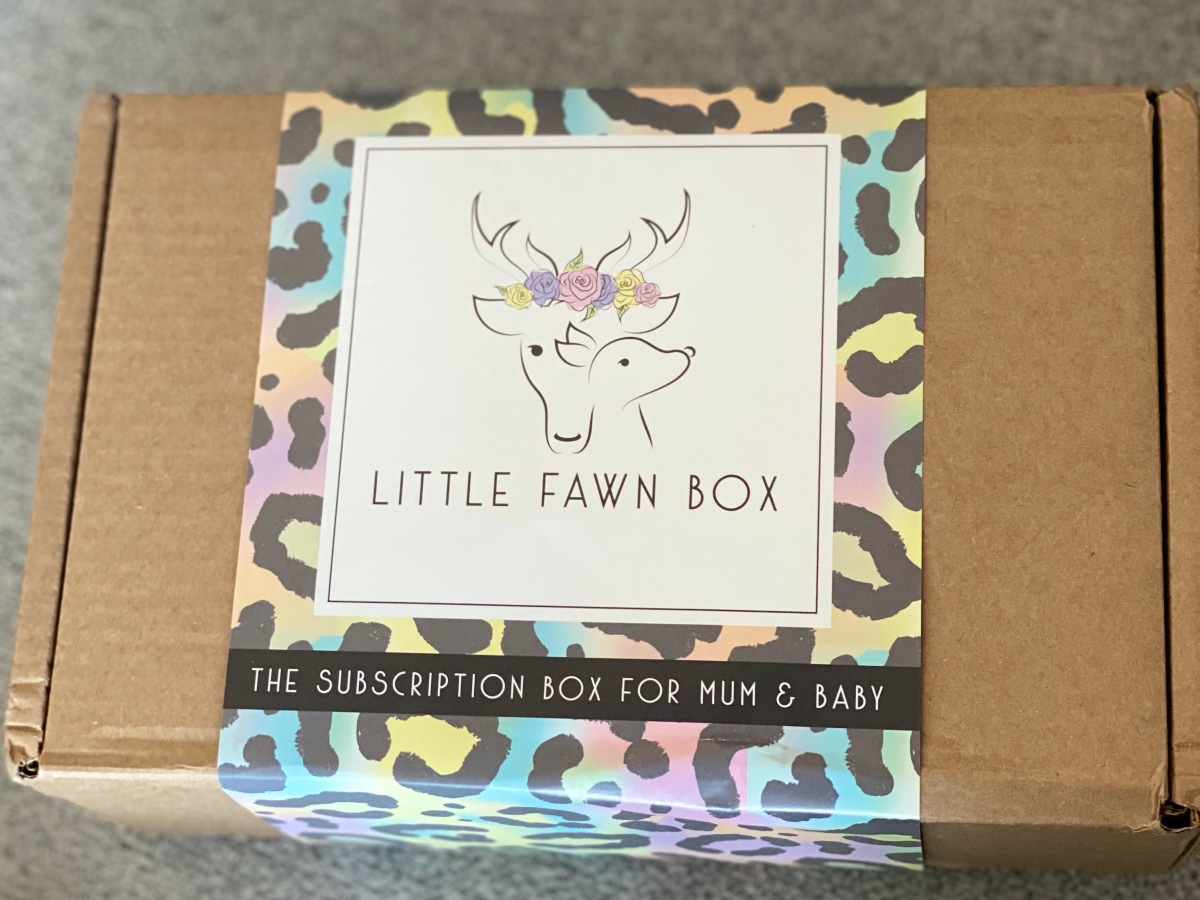 Photo of a brown box on a grey background with a multicoloured animal print sleeve wrapped around it. The sleeve also has a cream coloured square box with a drawing of a dears head with flowers one, and a fawn just in front of it. The words 'little fawn box' are in black underneath. There's also the words 'the subscription box for mum & baby' in cream on a black background underneath.