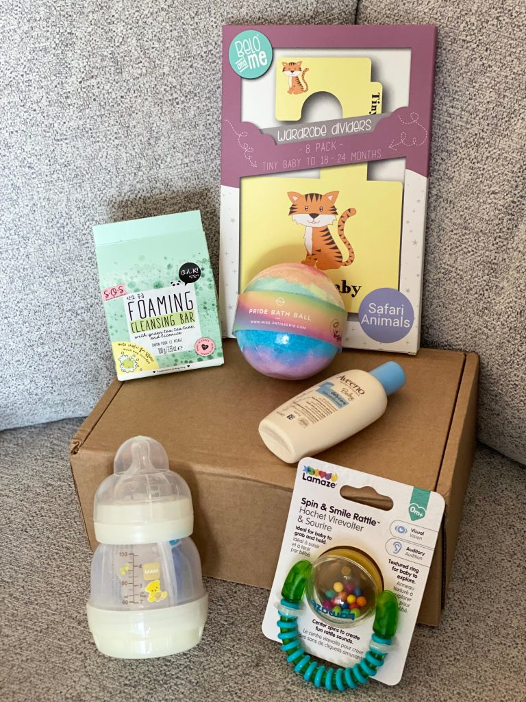 Photo of various baby products including a cream and see-through baby bottle, multi-coloured baby rattle and cream and blue coloured bottle containing baby body wash. There is also a green box containing a cleansing bar, a rainbow coloured bath bomb, and a purple, cream and yellow box containing wardrobe dividers which also has an orange black and white tiger on. The products are arranged on and around a brown box which is on a grey background.