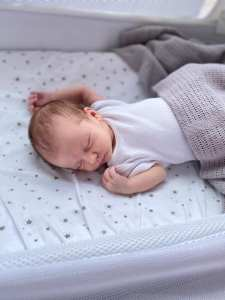 Alice, a small white baby with brown hair is wearing a white vest and laying on her back with her head turned to the side in her snuzpod, which has a white sheet with grey stars on the mattress. There is a grey blanket covering Alice and she is asleep.
