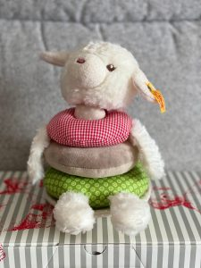 Photo of a cream coloured lamb shaped teddy bear with a smiley face on. The teddy bear has 3 rings making up its body; the top is red, middle light brown and bottom is green. The teddy bear is sitting on a grey box with red coloured drawings on.