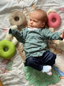 Alice, a small white baby with brown hair is laying on a multicoloured play mat wearing a green long sleeved top, dark blue leggings and white and light blue socks. Around her are a green ring, light brown ring and red ring.